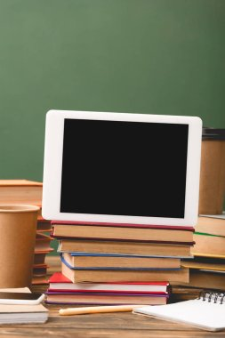 books, notebooks, pen, disposable cups, smartphone and digital tablet with blank screen isolated on green