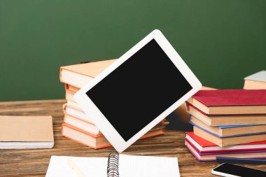 books, notebooks, smartphone and digital tablet with blank screen on wooden surface isolated on green