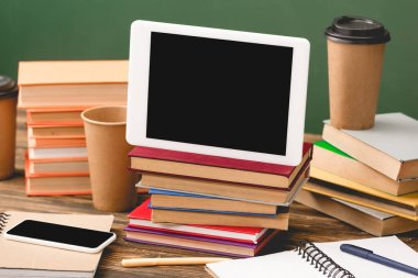 books, notebooks, pens, disposable cups, smartphone and digital tablet with blank screen on wooden surface isolated on green