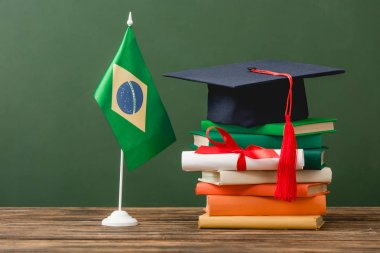 books, academic cap, diploma and brazilian flag on wooden surface isolated on green