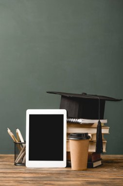 books, notebook, paper cup, academic cap and digital tablet with blank screen on wooden surface isolated on grey