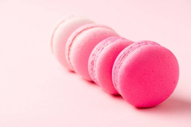 Selective focus of sweet colorful macarons on pink surface stock vector