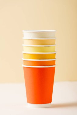 Colorful disposable cups on white surface isolated on beige stock vector
