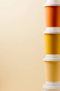 colorful disposable cups with white caps isolated on beige