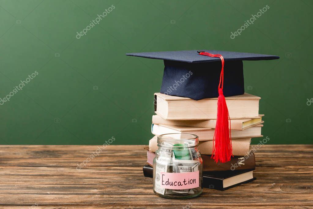 Books, academic cap and piggy bank on wooden surface isolated on green stock vector