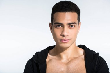 handsome mixed race man in black sports jacket looking at camera on white