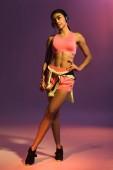 hezká Africká Američanka v růžové sportovní podprsence a sluchátka, která se v kameře pózala na fialovém pozadí