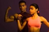 sporná africká americká žena a atletický smíšený závodní muž předvádějící biceps na tmavém pozadí