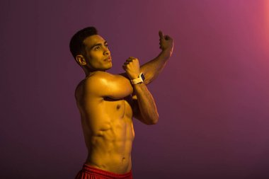 handsome sportive man in smart watch stretching on purple background