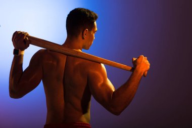 back view of shirtless sportive mixed race man with baseball bat on blue and dark purple gradient background