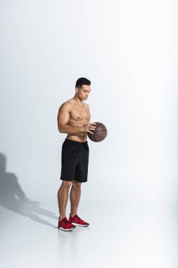 handsome shirtless mixed race man in black shorts and red sneakers holding ball on white