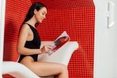 boční pohled na krásnou ženu v časopise pro čtení černých plavkách v lázeňském centru