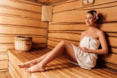 smiling barefoot girl in towel with flower in hair in sauna