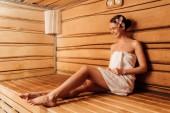 úsměv bosou dívku v ručníku s květinou ve vlasech v sauně