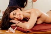 usmívající se žena užívající ájurvédské masáže v lázeňském centru