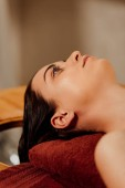 young woman lying on massage table in spa center