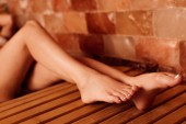 partial view of barefoot young woman in sauna