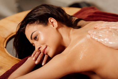 attractive young woman enjoying ayurvedic massage in spa center