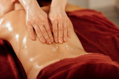 partial view of masseur doing ayurvedic massage in spa center