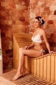 mladá žena v bílých bikinách na dřevěné lavičce v lázeňském centru