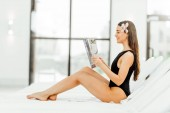 young woman reading magazine on sunbed in spa center