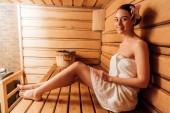 usměvavá žena v ručníku s květinou ve vlasech v sauně