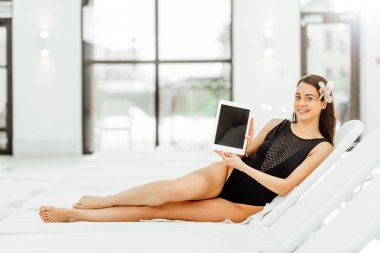 smiling barefoot woman lying on sunbed and showing digital tablet with blank screen