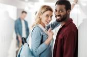 mosolygó többnemzetiségű hallgatók, akik az egyetemi folyosón állnak