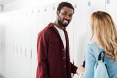 dva usmívající se multietnické studenty v chodbě blízko zámečníků na univerzitě