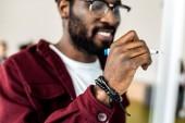 selektivní zaměření usmívajícího se afrického amerického studenta při psaní brýlí na flipchart
