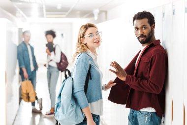 Smiling multiethnic students standing in corridor in college stock vector