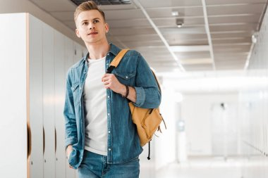 pensive student with backpack in corridor in university