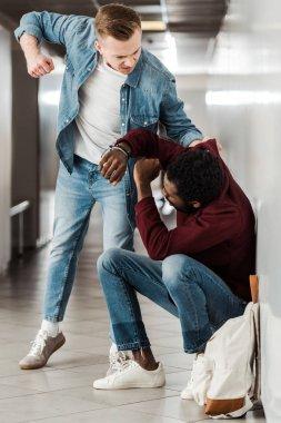 two multiethnic students fighting in corridor in college