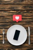 top view of smartphone with blank screen on white plate near paper cut card with heart symbol, knife and fork on brown wood surface