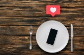 top view of  smartphone with blank screen on white plate near knife, fork and red paper cut heart with heart symbol on brown wooden surface