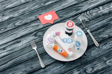 containers with social media logos on white plate near red paper cut card with heart symbol, knife and fork on grey wooden surface