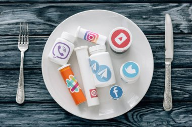 top view of container with social media logos on white plate near knife and fork on grey wooden surface