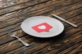 červená papírová karta se symbolem srdce na bílé desce blízko nože a vidlice na hnědém dřevěném povrchu