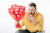 pohledný muž držící cigaretovou krabičku s logem Instagram a kytice červeného papíru vystřihněte karty se symboly srdcí izolovanými na bílém