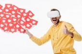 Fotografie aufgeregter Mann im Virtual-Reality-Headset, der den Daumen nach oben zeigt, während er rote, papiergeschnittene Karten mit Herzsymbolen auf weißem Hintergrund hält