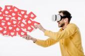 Fotografie aufgeregter Mann mit Virtual-Reality-Headset, während er rote Karten mit Herzsymbolen auf weißem Papier hält