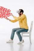 Fotografie aufgeregter Mann in Virtual-Reality-Headset sitzt auf Stuhl und hält rote Karten mit Hertssymbolen auf weißem Hintergrund