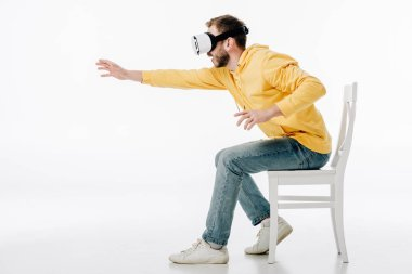 young man in virtual reality headset sitting on chair with outstretched hand on white background