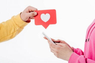 cropped view of man holding red paper cut card with heart symbol and woman using smartphone isolated on white