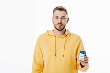 handsome young man in yellow hoodie holding cigarette pack with facebook logo isolated on white