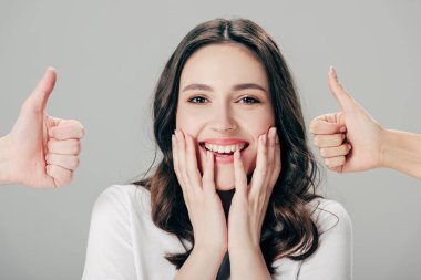cropped view of man and woman showing thumbs up near excited girl isolated on grey