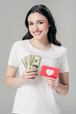 beautiful smiling girl holding dollar banknotes and red paper cut card with heart symbol isolated on grey