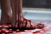 cropped view of barefoot bleeding woman in bathroom