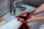 partial view of woman washing bleeding hands in bathroom