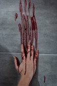 bleeding hand and blood print on grey wall